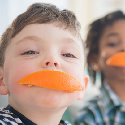 Boy smiling with orange in his mouth