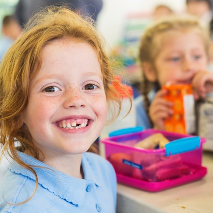 girl smiling with lunch box