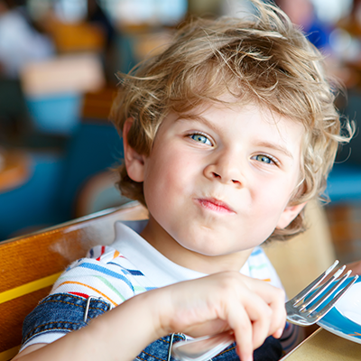 boy smiling with fork in hand