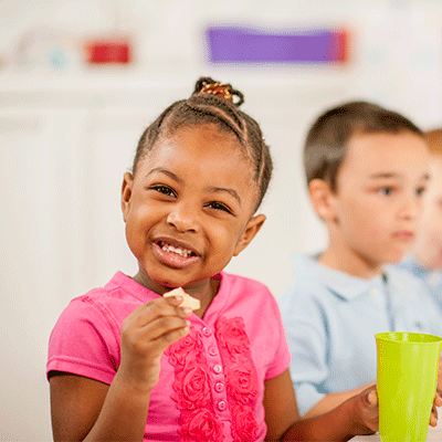 Girl with brown hair smiling and eating lunch