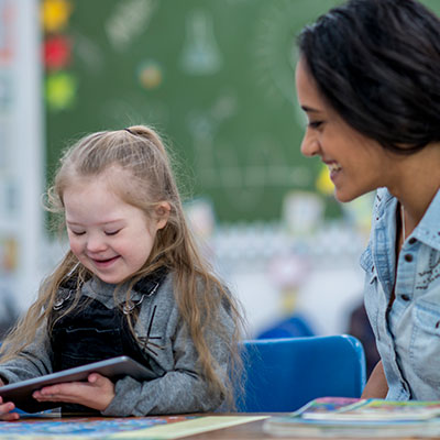 Girl with special needs on iPad with teacher