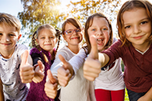 kids smiling in a row with thumbs up